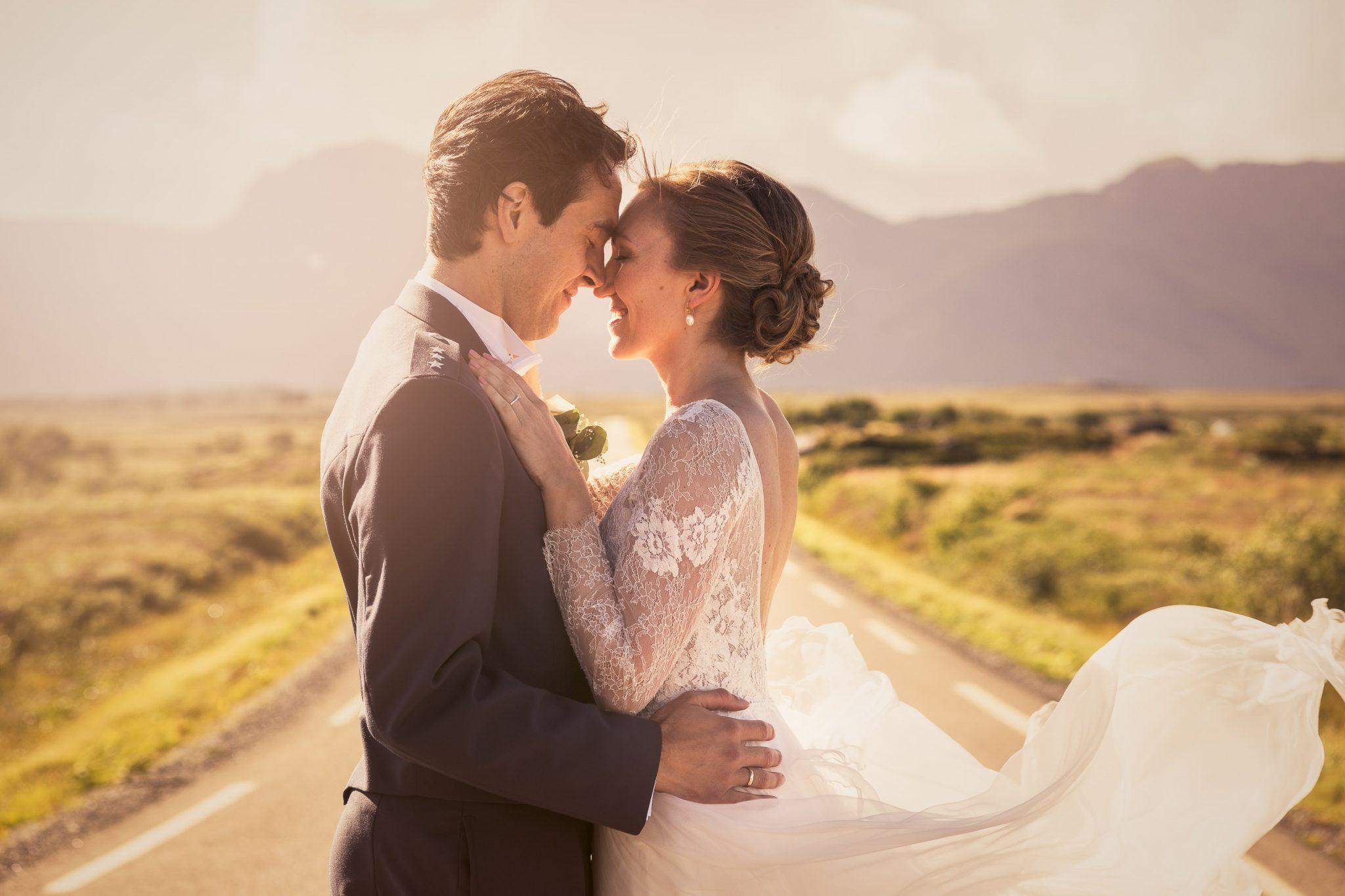 Brudepar står på en vei i Lofoten med fjell i bakgrunnen og vind i kjolen