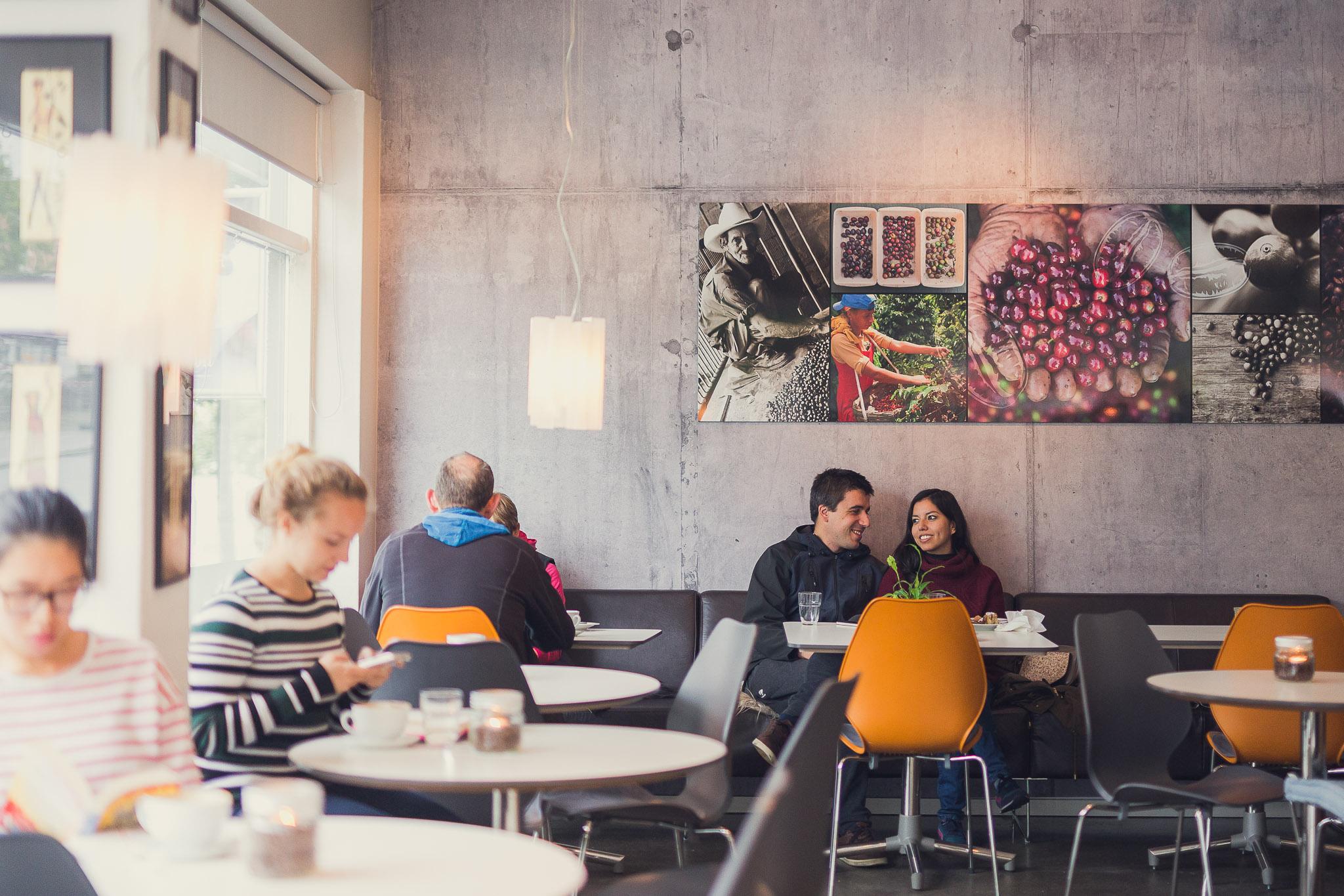 To besøkende sitter i sofaen med en kopp kaffe hos Babel i Bodø