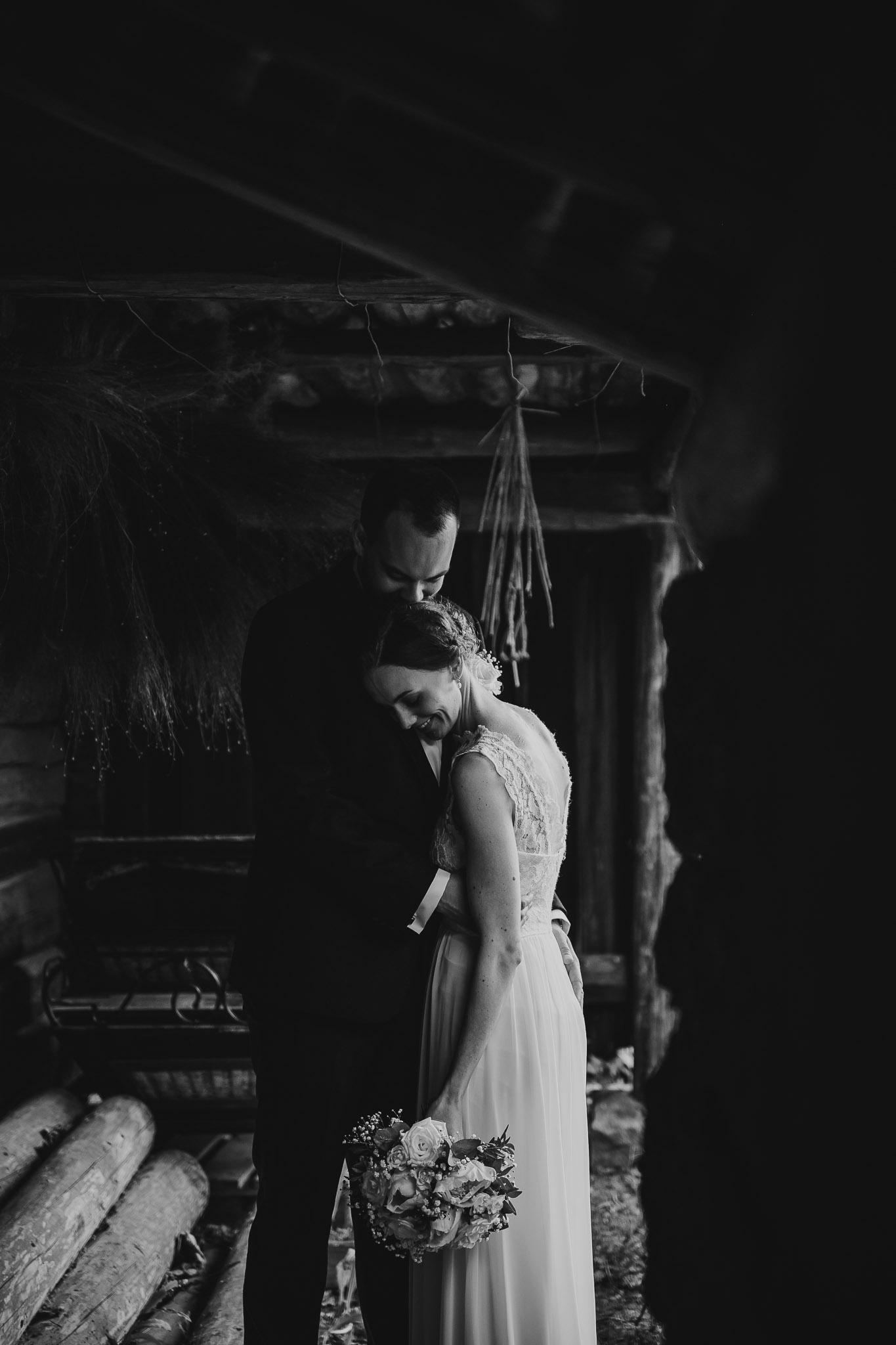 Hvit brud står inntil sin nye ektemann i en mørk låve