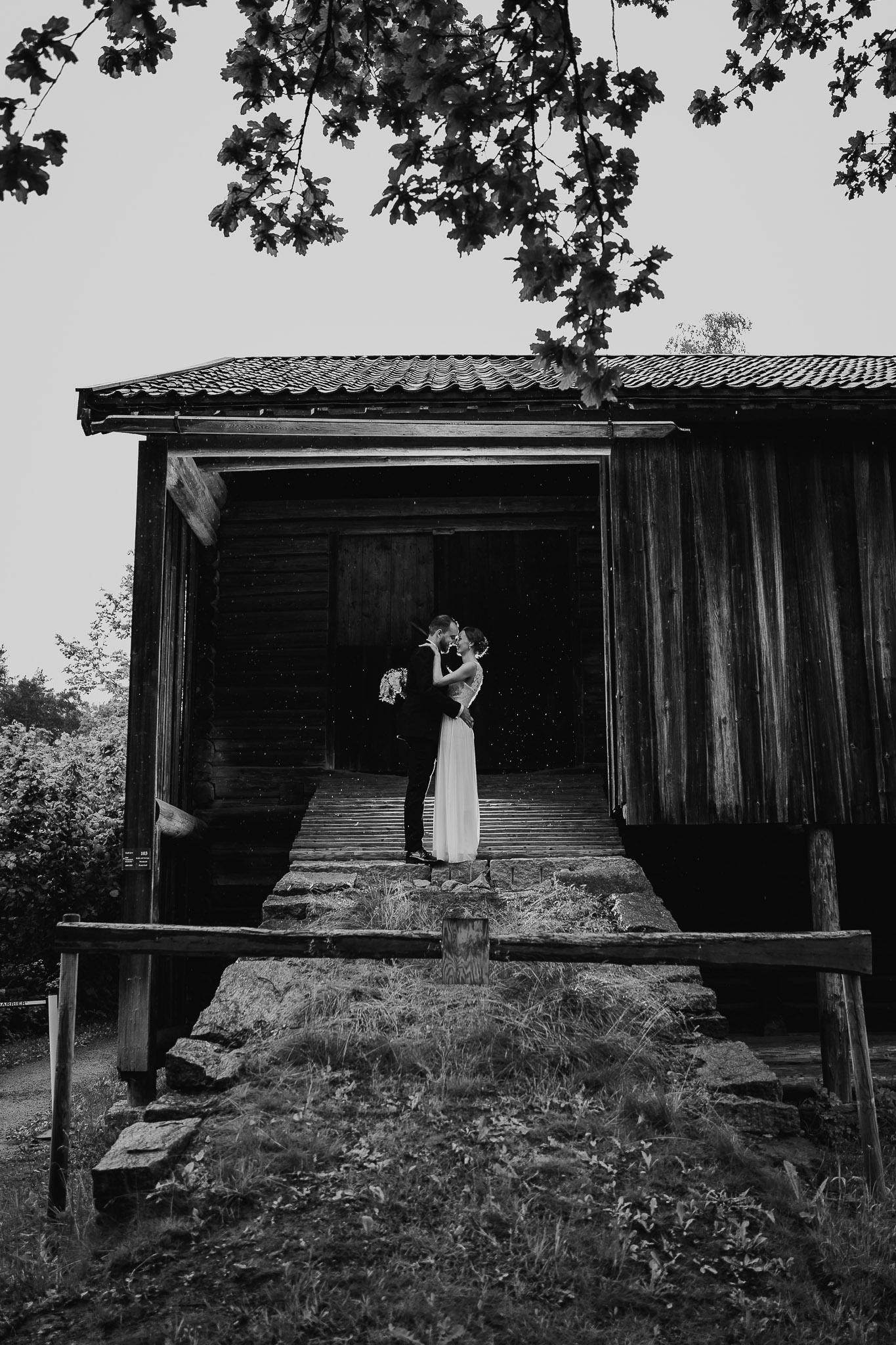 Brudepar i bryllupskjole og dress står i åpningen av en låve og kysser