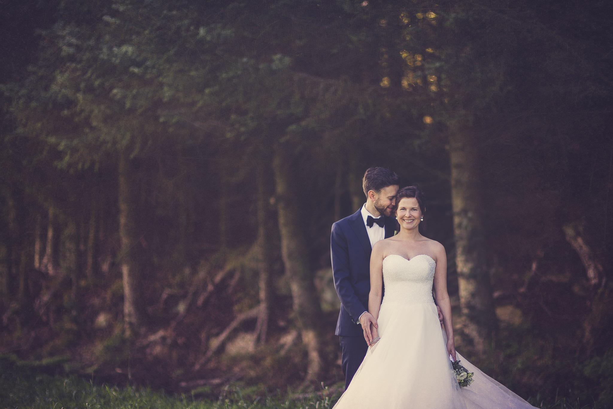 Brudepar står fremfor en mørk granskog på Meløya