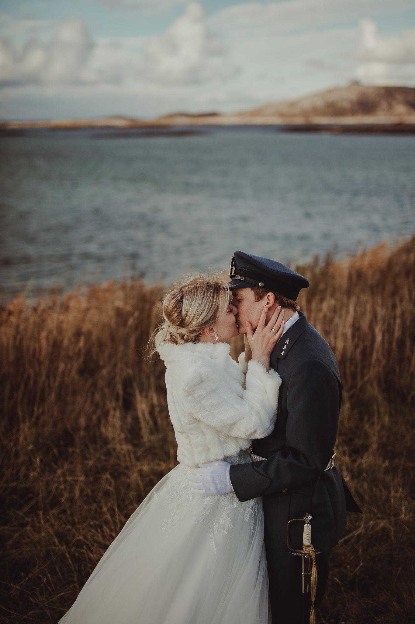 Brudepar kysser med havet i bakgrunn i Bodø