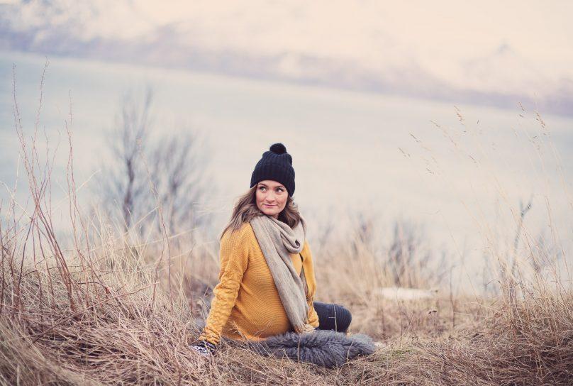Gravid jente i gul genser, skjerf og sort lue sitter på gresset foran havet i Bodø