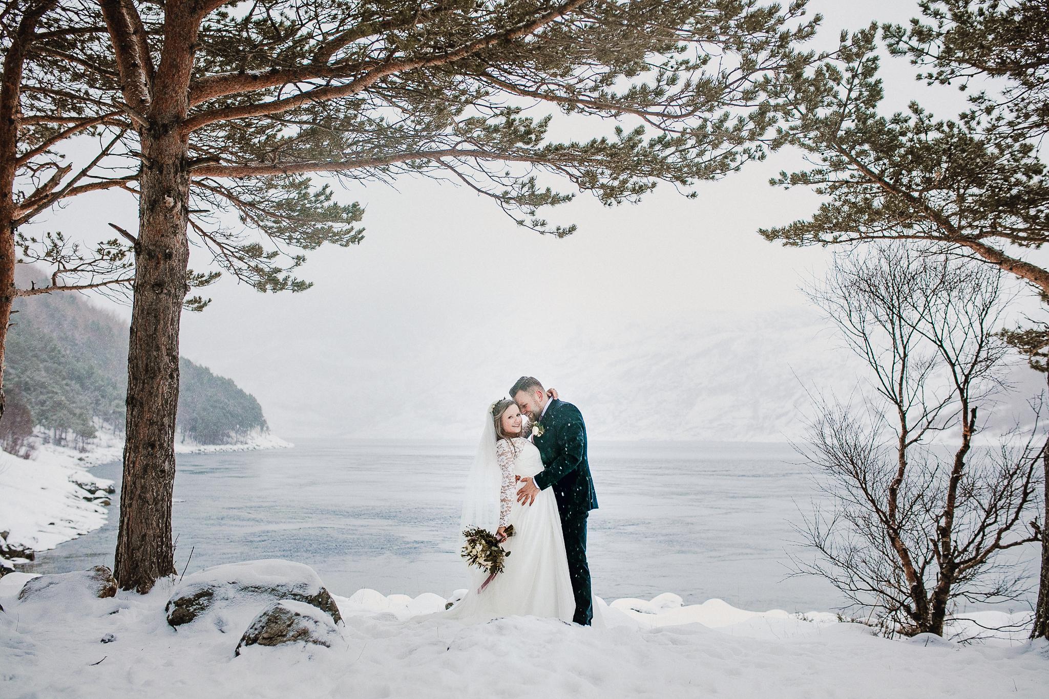Brudepar omfavner hverandre under flere furutrær foran sjøen i snøvær.