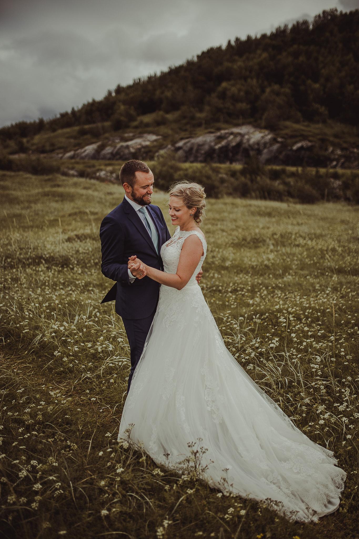 Brudepar danser på en eng full av hvite blomster