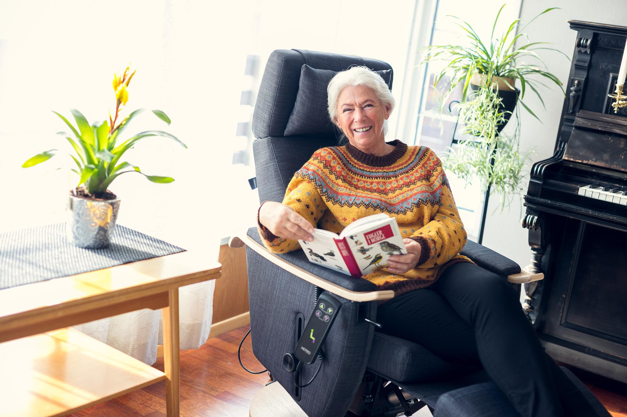 Dame sitter i en Hepro hjelpestol og leser et blad