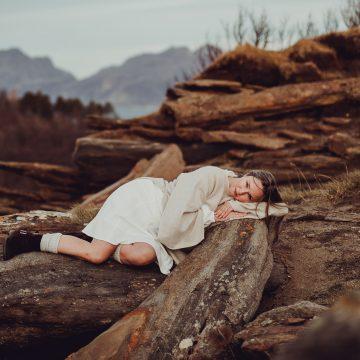Dame i hvite klær ligger sammenkrøket på en stein i Bodø