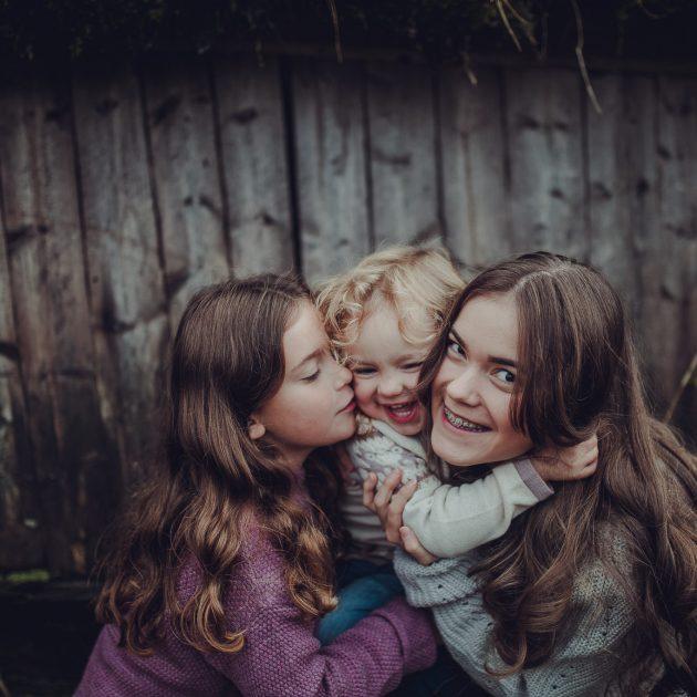 Tre søstre klemmer hverandre og ler mens den minste blir kilt