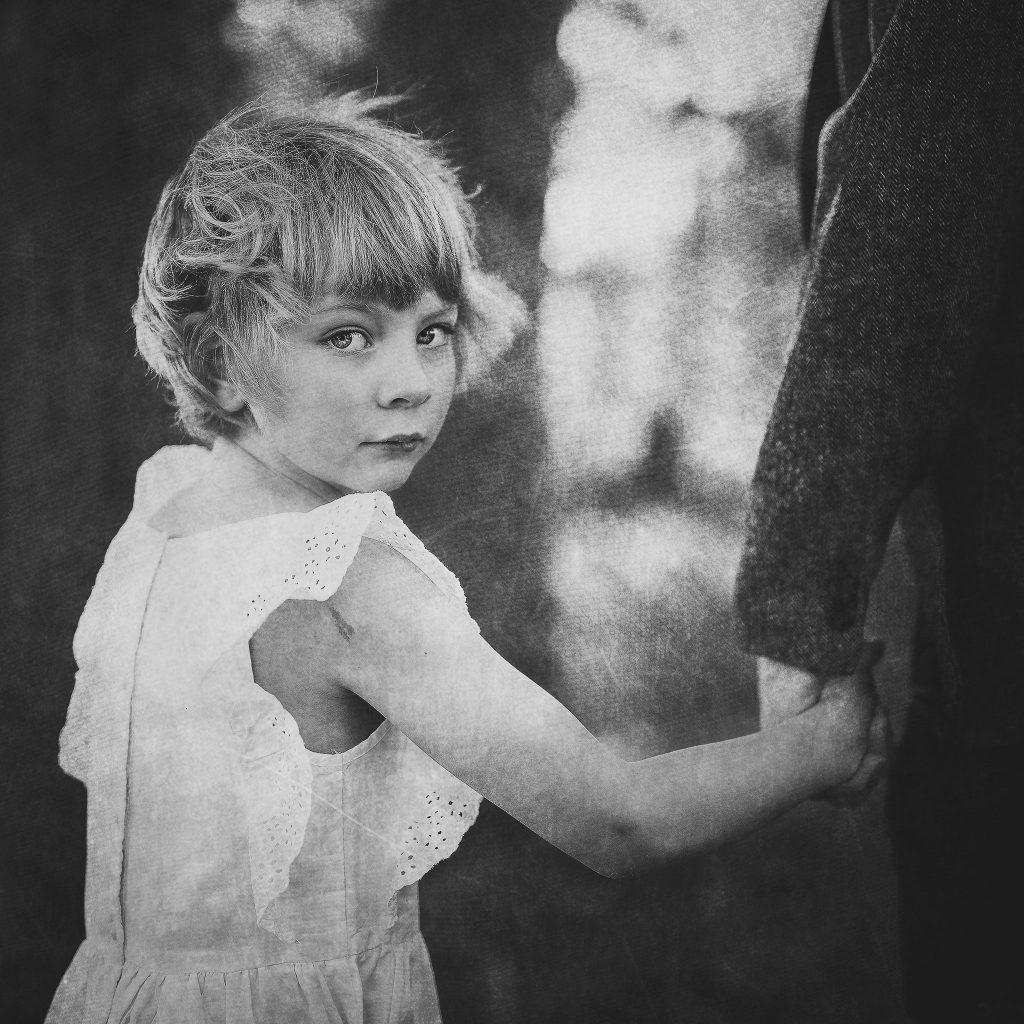 Liten jente i hvit kjole holder hånden til en skummel mann mens hun ser bakover