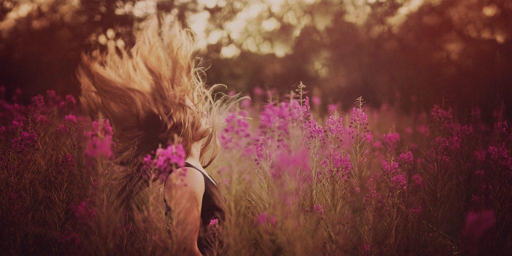 Jente kaster håret bakover i en blomstereng