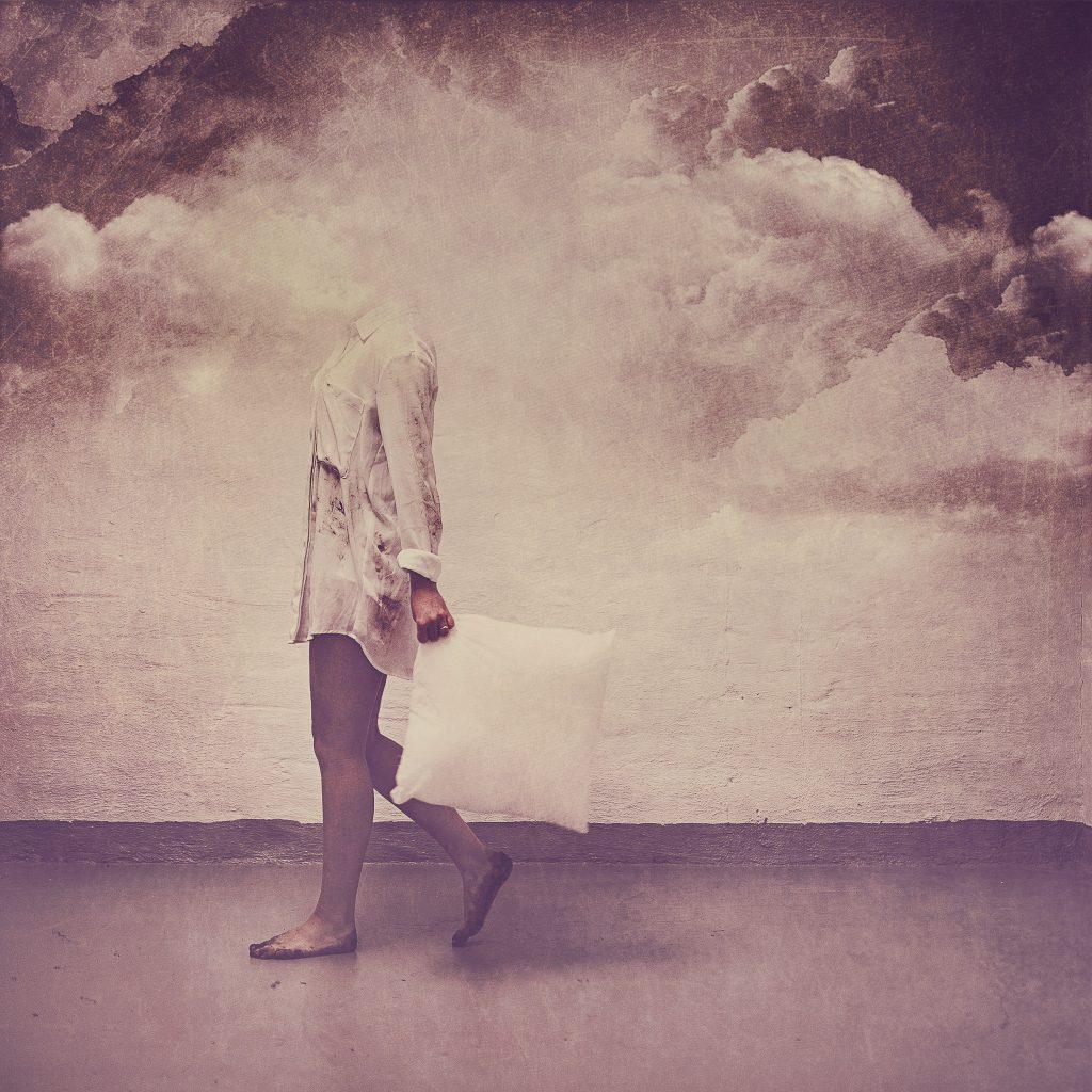 Jente med skitne føtter og skyer over hodet bærer en pute i armen