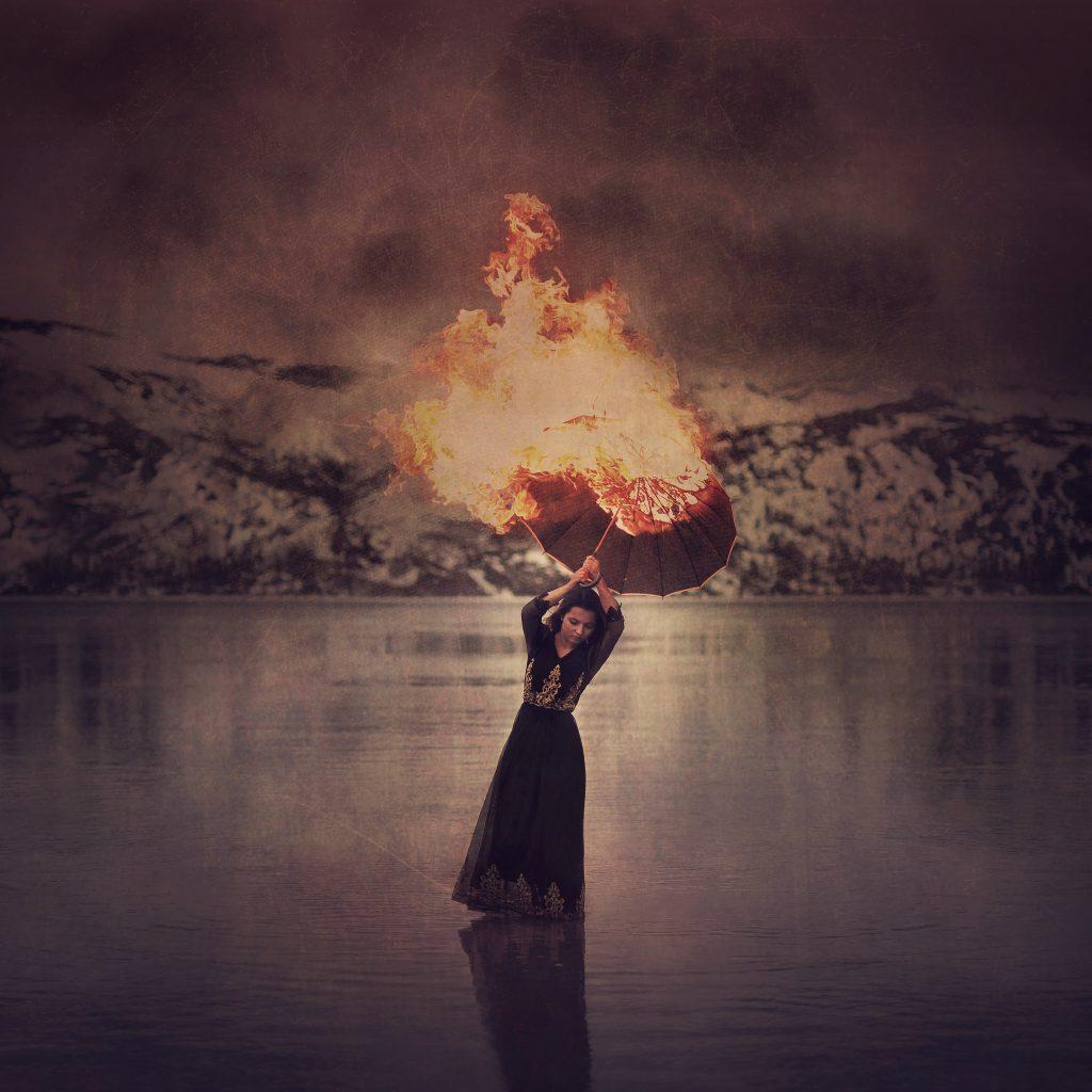 Jente i sort kjole står i vannet og holder en brennende paraply i lufta