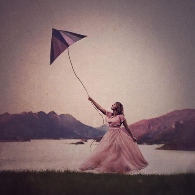 Jente i rosa kjole flyver en drage gjennom luften
