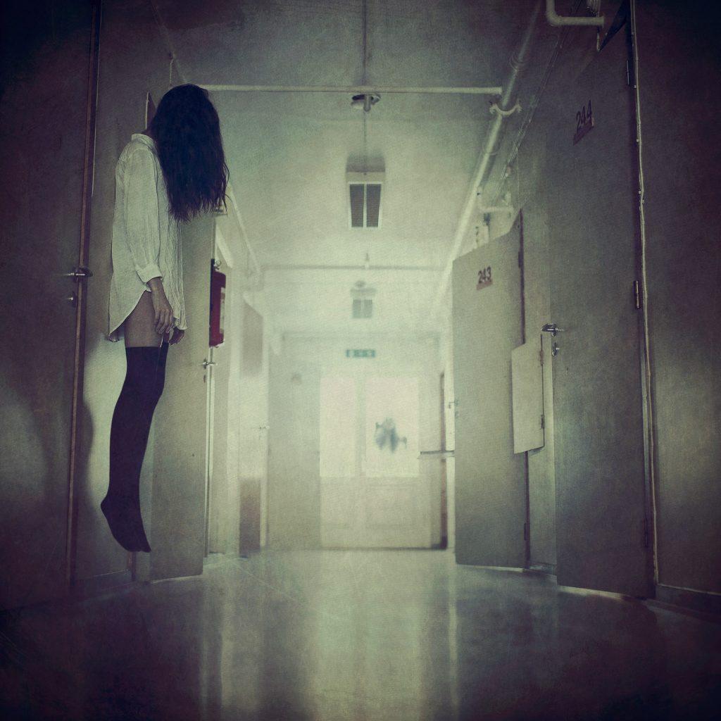Jente henger på veggen i en korridor i et asylum