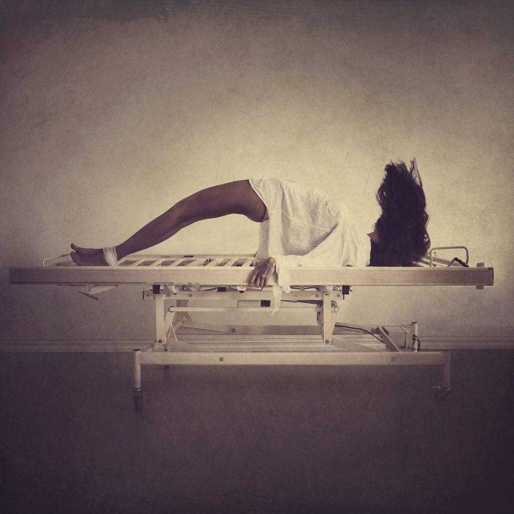 Jente besatt av en demon er lenket fast i en seng i et asylum