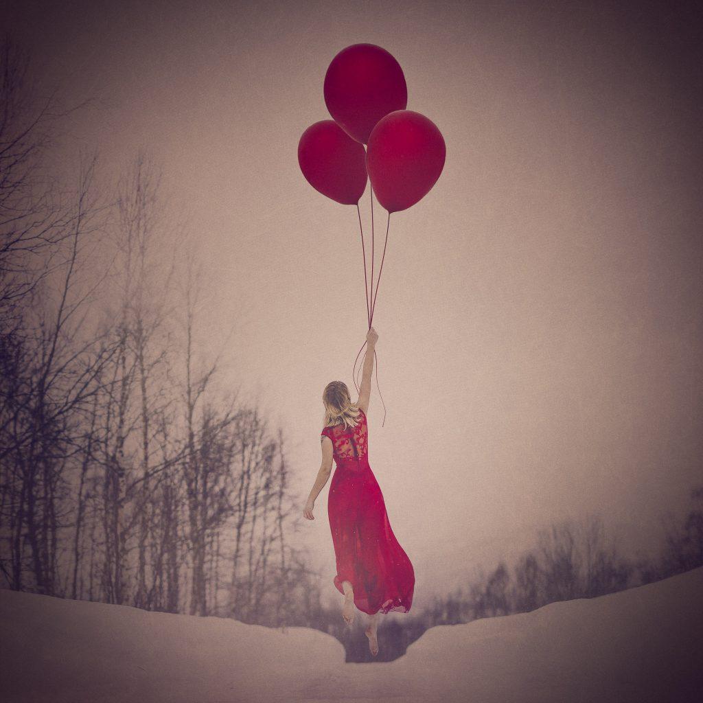 Fine Art jente i rød kjole henger magisk i lufta etter en rød ballong