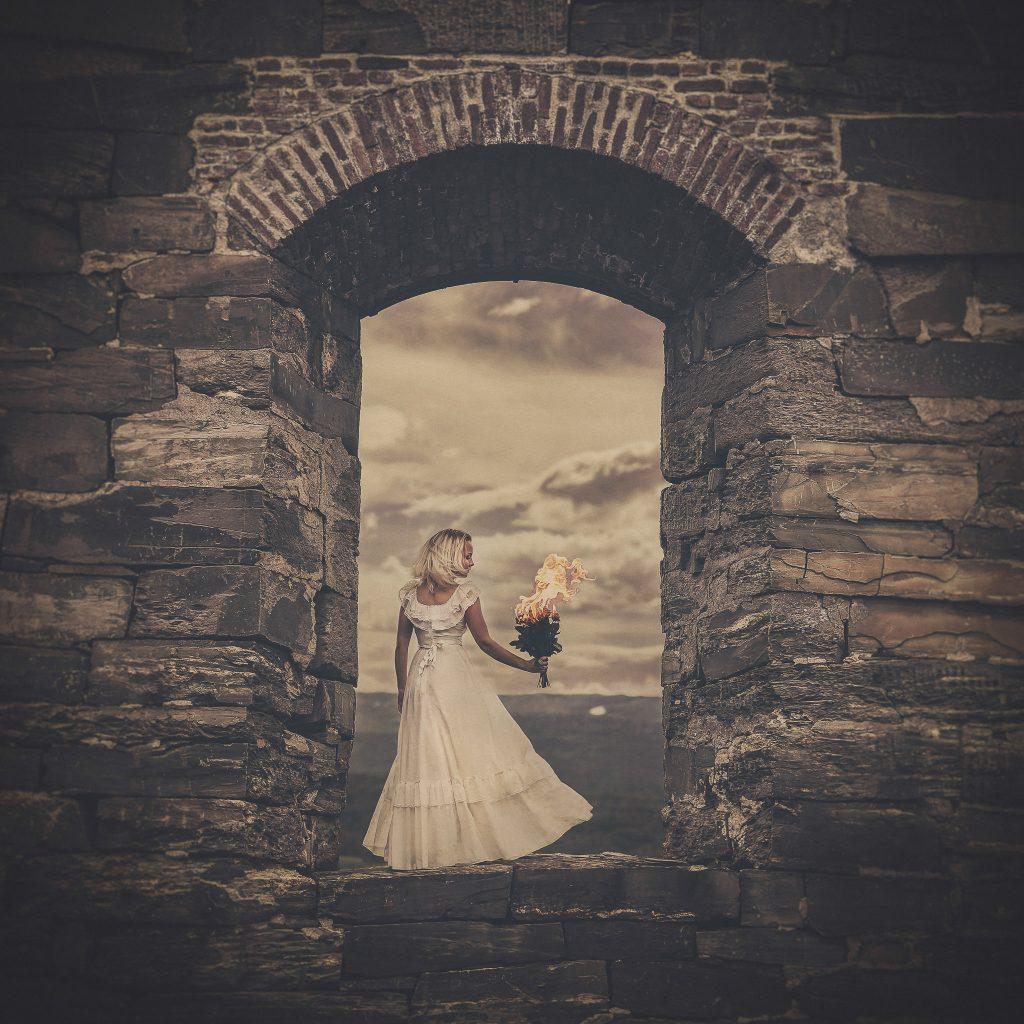 Kunstnerisk jente i brudekjole står i åpningen av en murvegg og holder en brennende bukett
