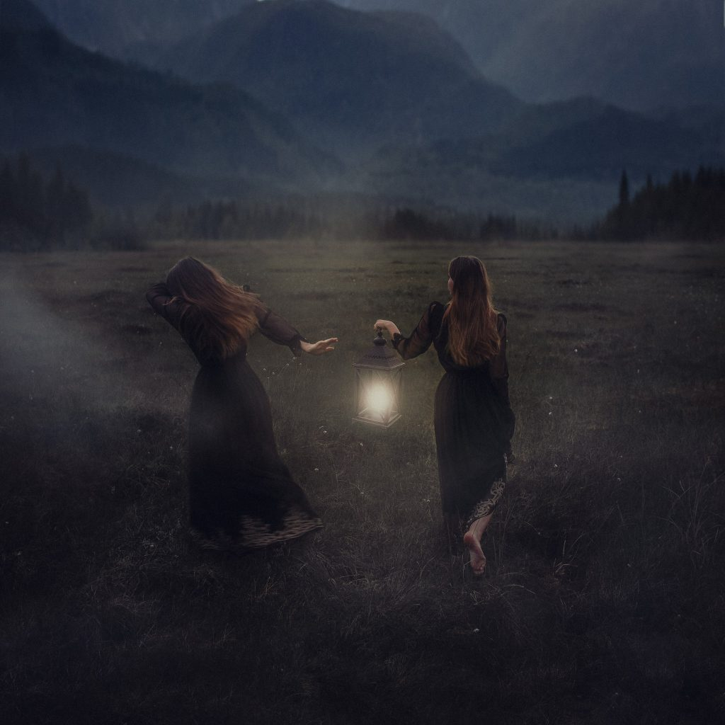 To jenter løper på en tåkete myr med en lanterne som lyskilde