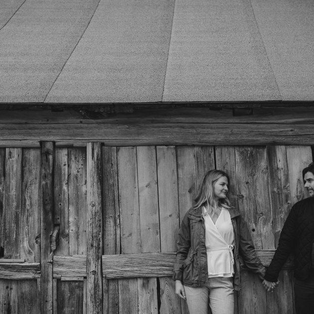 Kjærestepar holder hender fremfor et stabbur ved Fauske Bygdetun